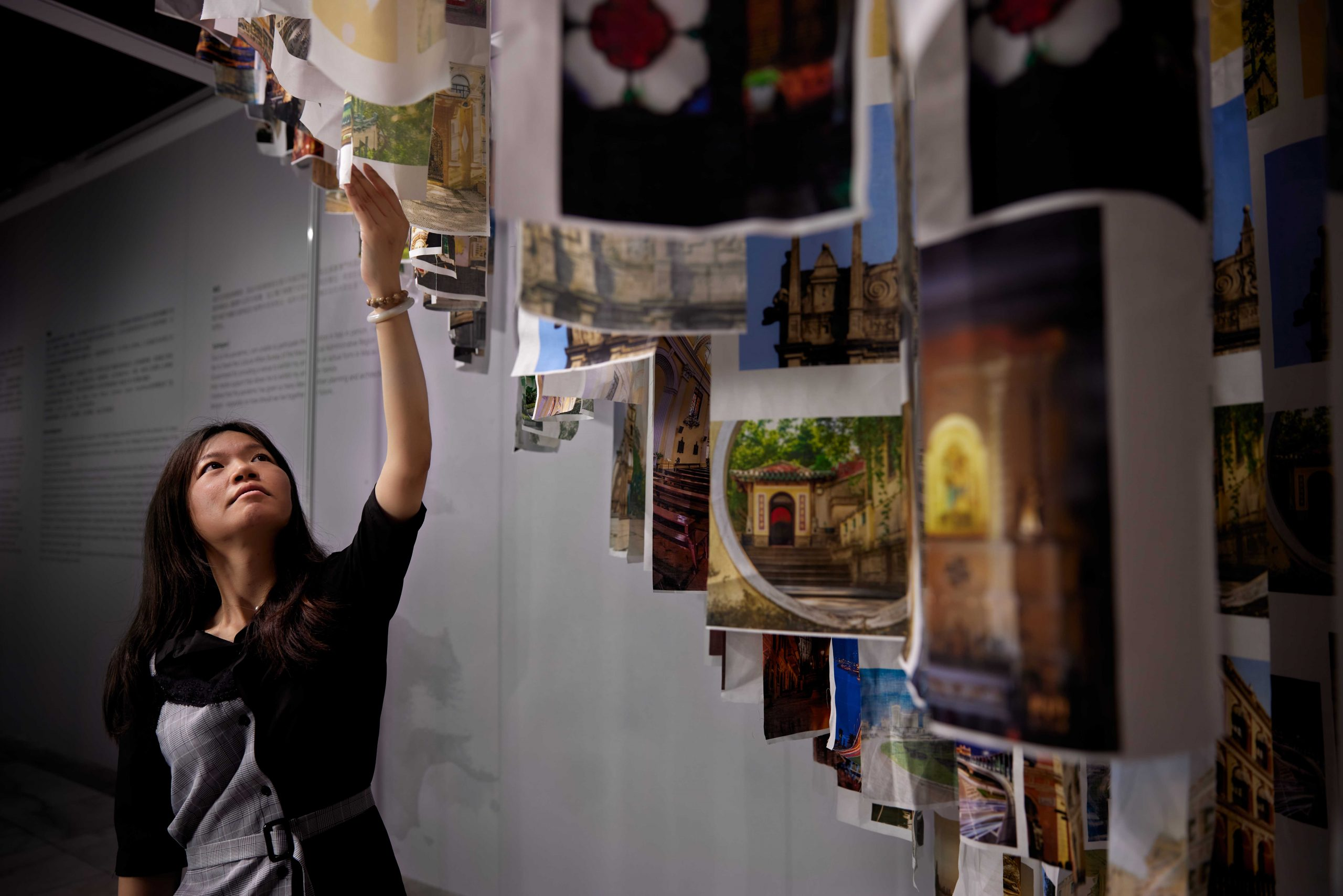 Ina Lao Man Si reaching up to one of the canvas pieces in her 'Coexistence' exhibition