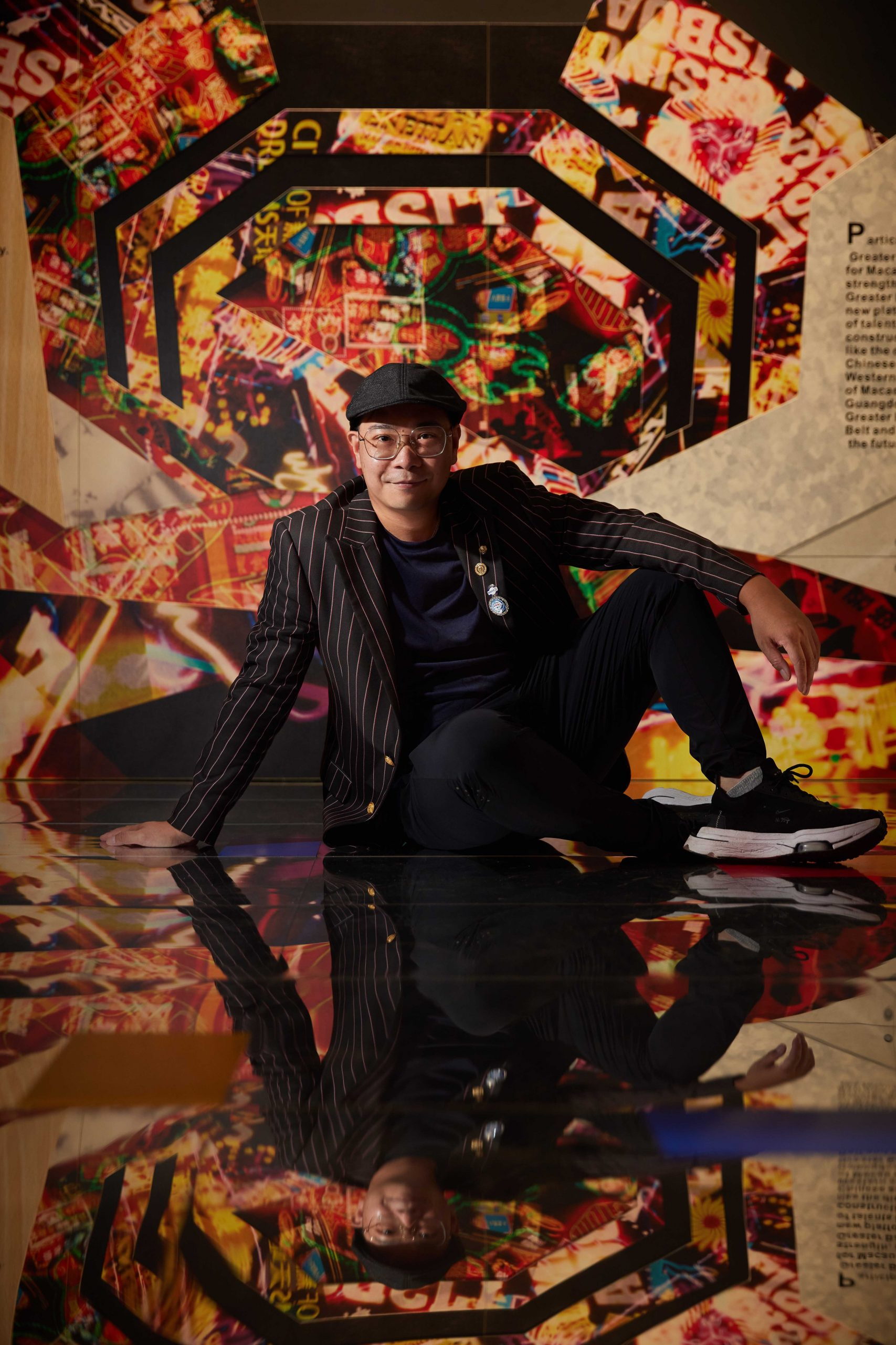 Chan Ka Tat sitting on the mirrored, multi-colour floor in his 'Connected' exhibition